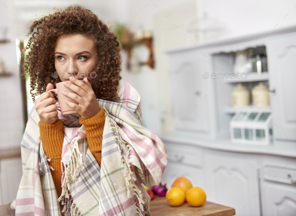 Young woman wrapped in blanket drinking hot tea - Stock Photo - Images