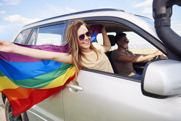 Smiling woman with rainbow flag traveling by car in summertime - Stock Photo - Images