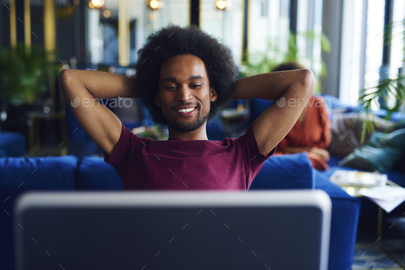 Satisfied African man relaxing in the office - Stock Photo - Images