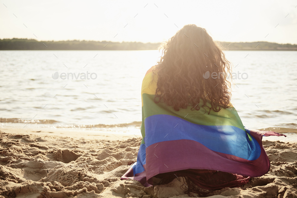 Rear view of young woman covered with rainbow flag - Stock Photo - Images
