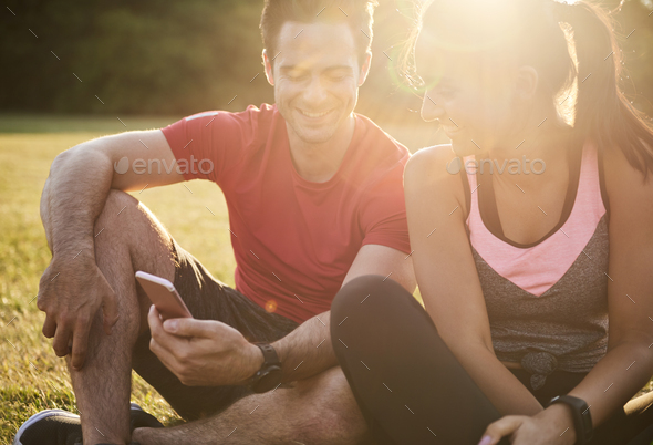 Happy couple using mobile phone after hard workout - Stock Photo - Images