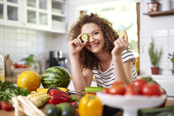 Woman holding a slice of cucumber - Stock Photo - Images