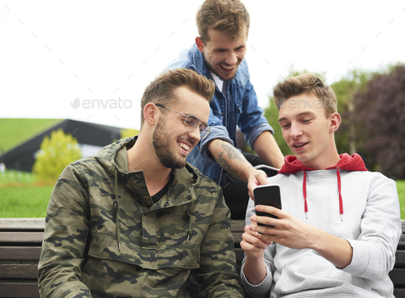 Happy men looking at smart phone and sitting on bench - Stock Photo - Images