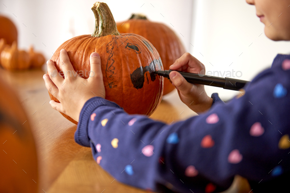 Close up of child drawing on halloween pumpkin - Stock Photo - Images