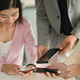 Young office workers are using smartphones to exchange social media data. - PhotoDune Item for Sale