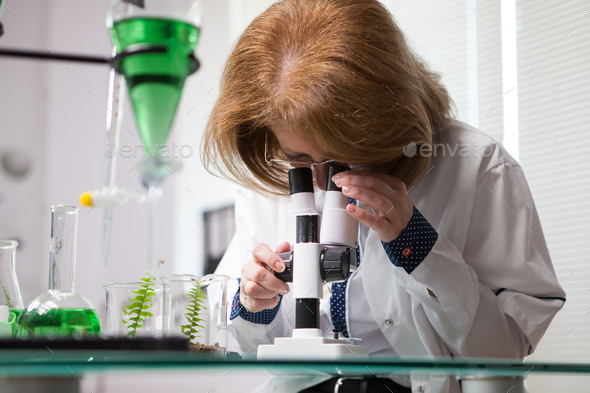 Female in microbiological industry adjusting her microscope - Stock Photo - Images