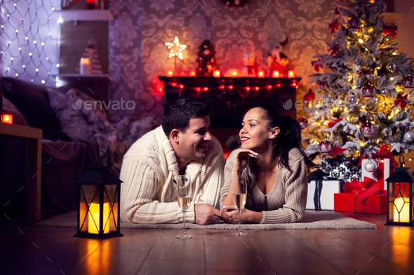 Photo of young couple resting by the fireplaec in the christmas room - Stock Photo - Images