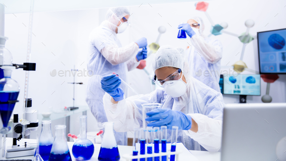 Three scientists analyzing several containers with blue liquid - Stock Photo - Images