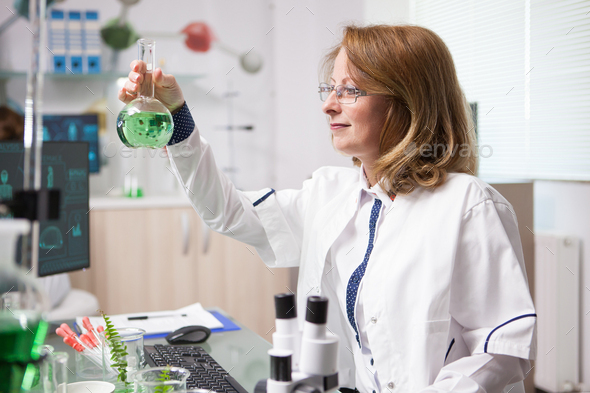 Middle age female biologist in a laboratory looking at chemical test tube - Stock Photo - Images