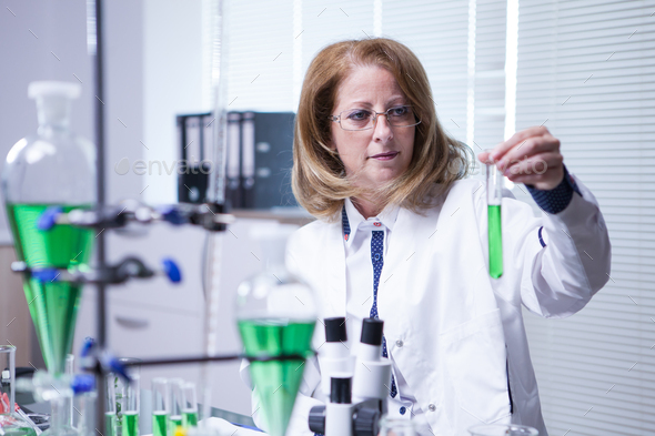 Female scientist wearing a white coat in a research lab - Stock Photo - Images