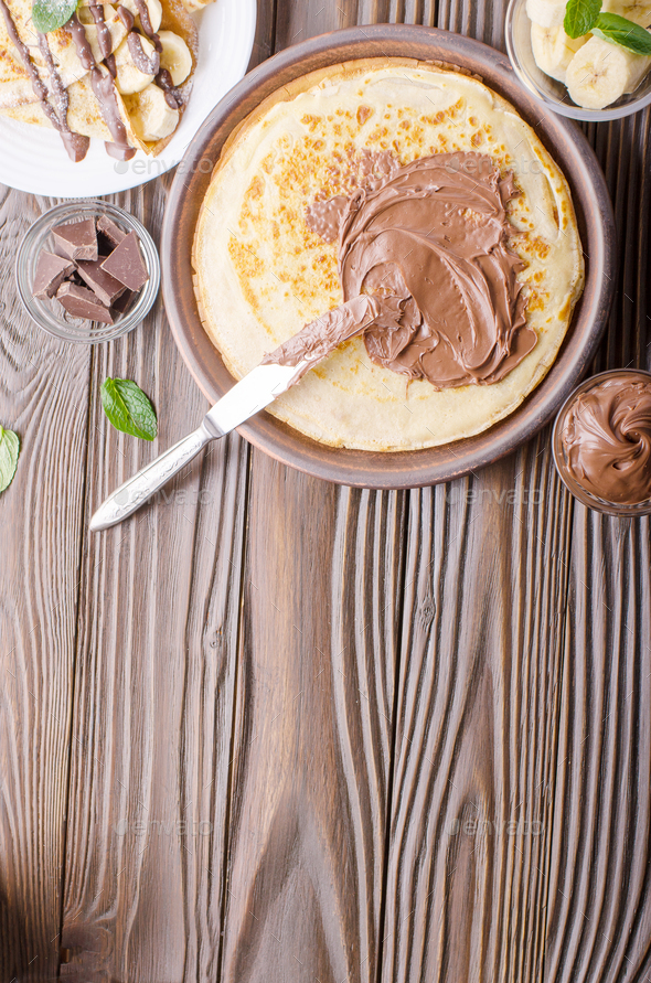 Flat lay French crepes with chocolate sauce and banana in clay bowl on wooden kitchen table - Stock Photo - Images