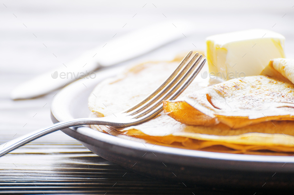 Stack of French crepes with butter in ceramic dish on wooden kitchen table - Stock Photo - Images