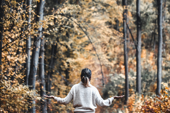 Autumn girl standing backwards and watching nature. Autumn forest colors with girl back view - Stock Photo - Images