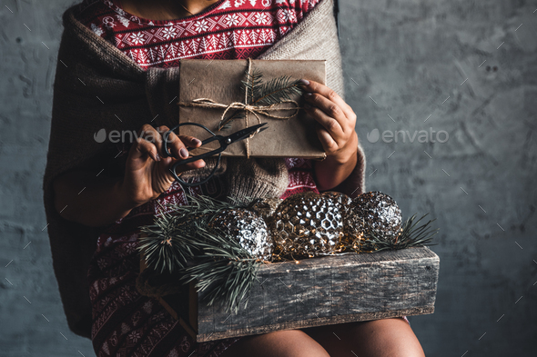 Girl in a Christmas dress holds balls in a wooden box, holiday, comfort - Stock Photo - Images