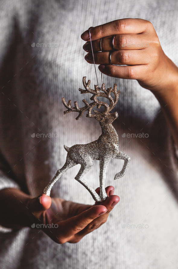 Woman in warm sweater holding toy deer decorative ball in hands, copy space. Christmas, new year - Stock Photo - Images