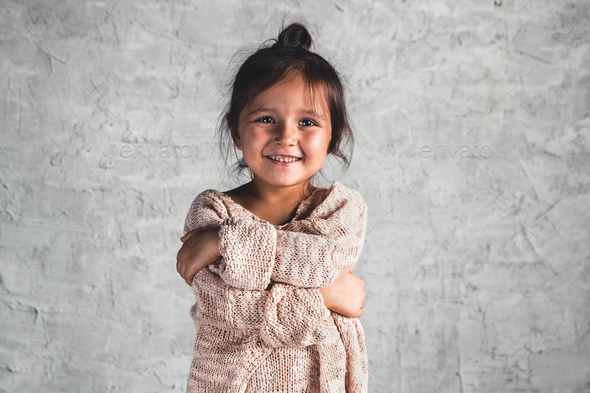 Portrait of a charming little girl in beige sweater on gray background - Stock Photo - Images