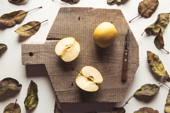 Yellow apples on a sliced board in vintage style. leaves, food, wholesome food, vegan, farm product - Stock Photo - Images