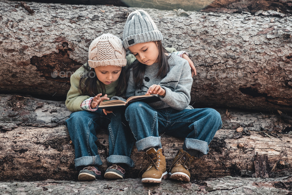 Two little girls reading books, sitting on a log. ?oncept of education and friendship - Stock Photo - Images