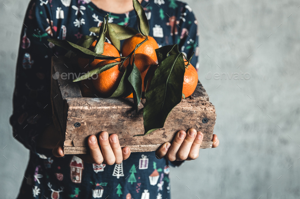 Kids hands holds wooden box with fresh clementine tangerines top view, copy space - Stock Photo - Images