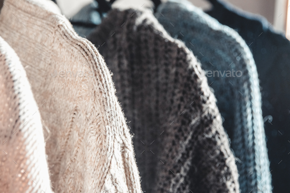 Collection of warm sweaters hanging on rack against graybackground, closeup - Stock Photo - Images