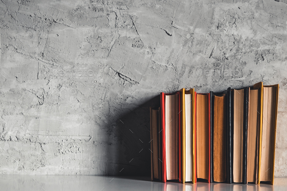 Education and reading concept - group of colorful books on the white table on the gray background - Stock Photo - Images