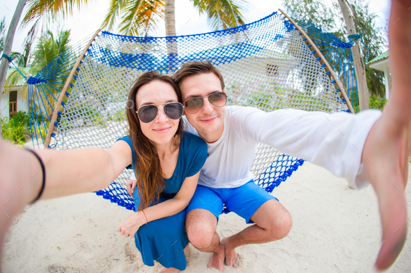 Happy couple making selfie relaxing in hammock - Stock Photo - Images