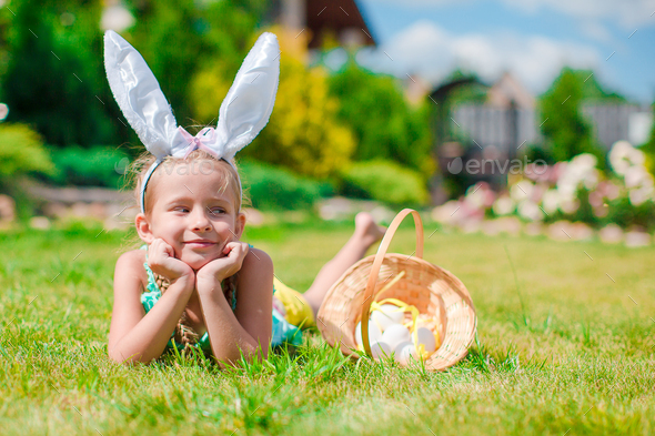 Adorable little girl wearing bunny ears and basket with Easter eggs - Stock Photo - Images