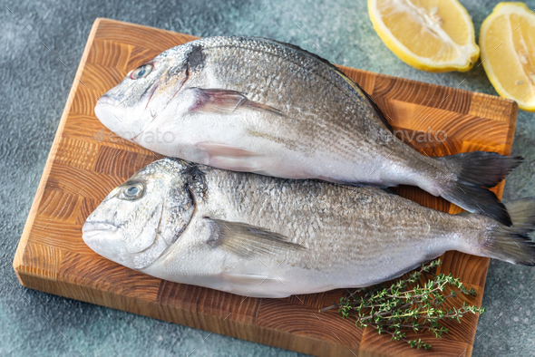 Fresh dorada on the wooden board - Stock Photo - Images