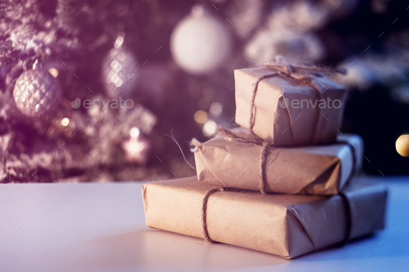 Stacks of Christmas presents with decorated Christmas tree in background - Stock Photo - Images
