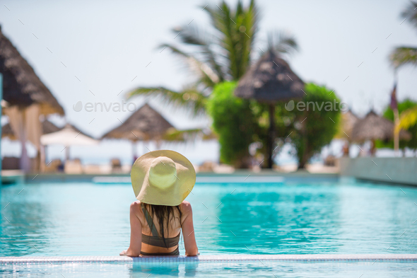 Beautiful young girl relaxing in outdoor swimming pool - Stock Photo - Images