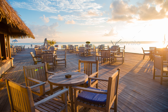 Summer empty open air restaraunt near sea at exotic island on beautiful sunset - Stock Photo - Images