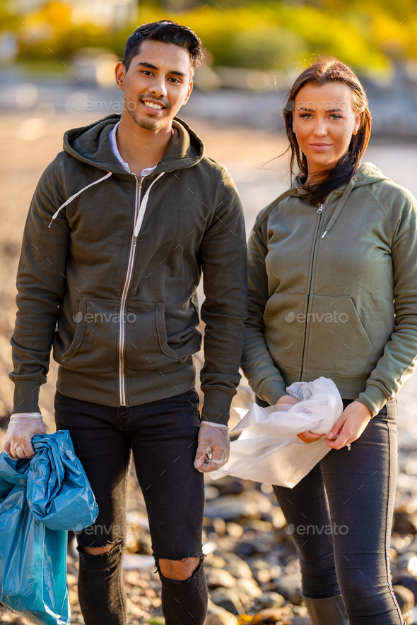 Young multi-ethnic environmental volunteers standing at beach - Stock Photo - Images