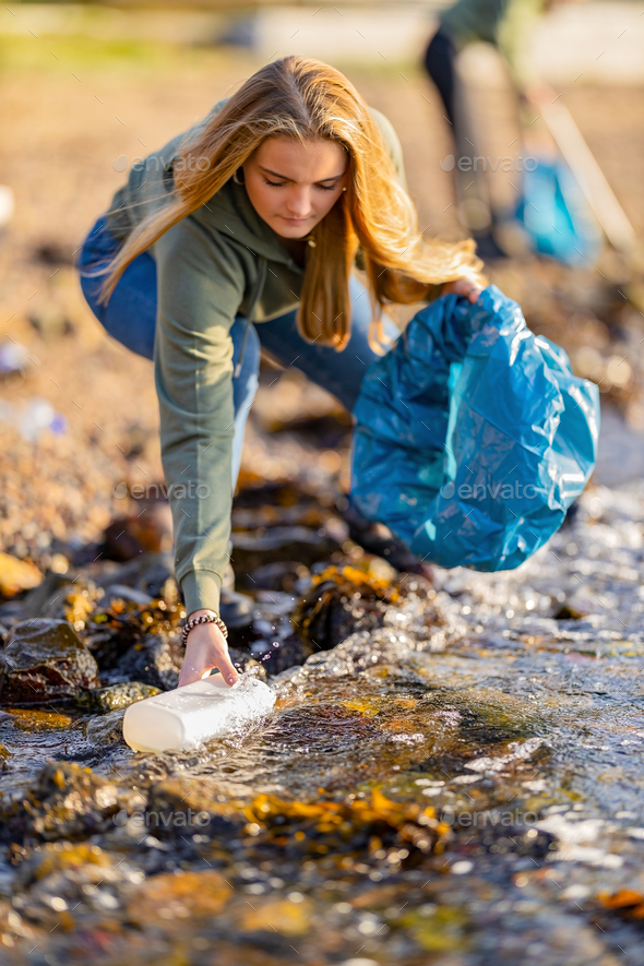 Young woman picking up garbage from rocky shore - Stock Photo - Images