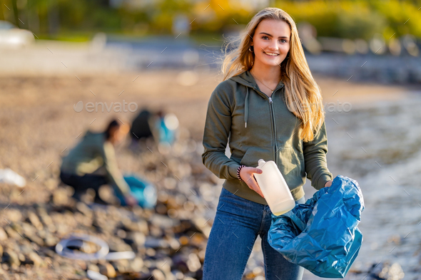 Volunteer holding bottle and garbage bag at beach - Stock Photo - Images