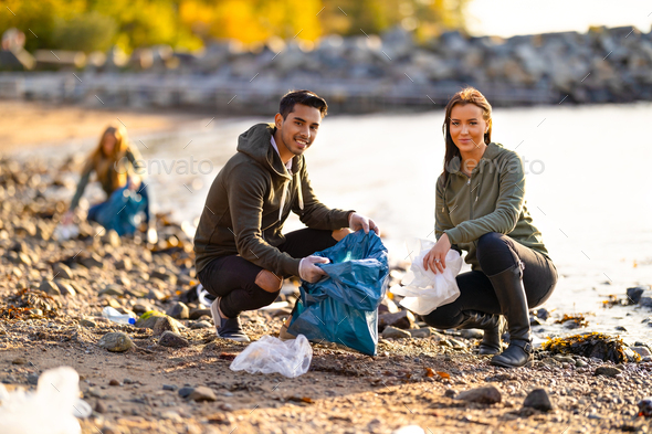 Portrait of smiling environmental protection volunteers cleaning beach - Stock Photo - Images
