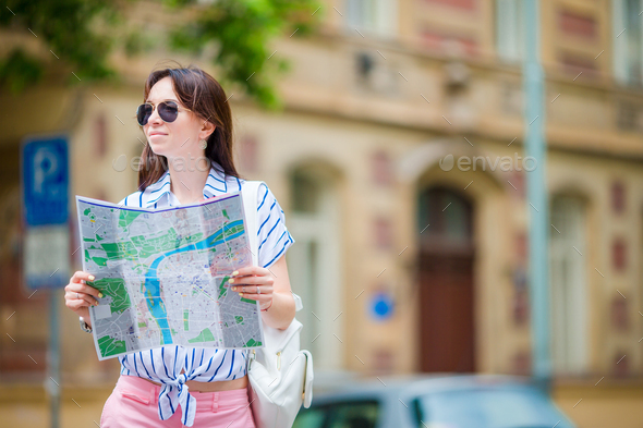 Happy young woman with a city map in Europe. Travel tourist woman with map in Prague outdoors during - Stock Photo - Images