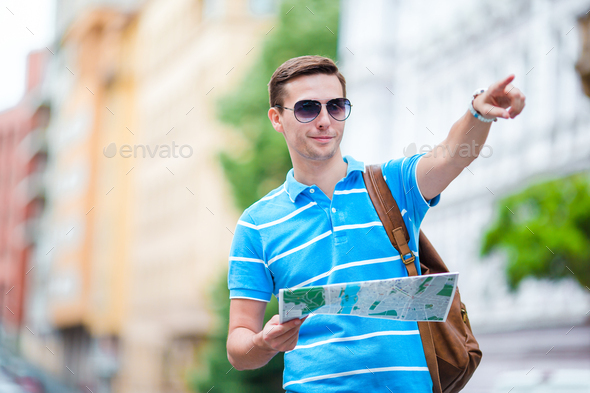 Man tourist with a city map and backpack in Europe. Caucasian boy looking at the map of European - Stock Photo - Images