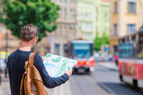 Young man with a city map and backpack in Europe. Caucasian tourist looking at the map of European - Stock Photo - Images