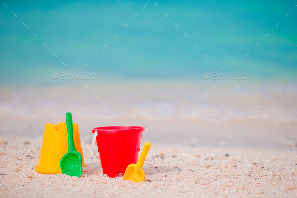 Kid's beach toys on white sand. Buckets and blades for kids on the white sandy beach after - Stock Photo - Images