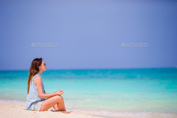Beautiful woman in a meditation on the beach. Happy girl in yoga position relaxing on tropical beach - Stock Photo - Images