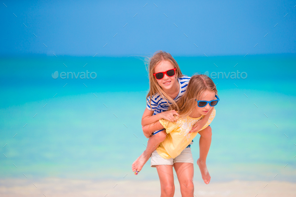 Adorable little caucasian girls at beach during summer vacation. Happy kids having fun together on - Stock Photo - Images