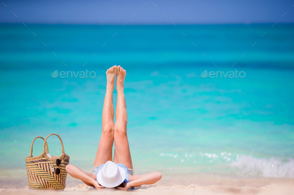 Young beautiful girl relaxing on white beach. Tourist woman enjoy beach vacation lying on the sand - Stock Photo - Images