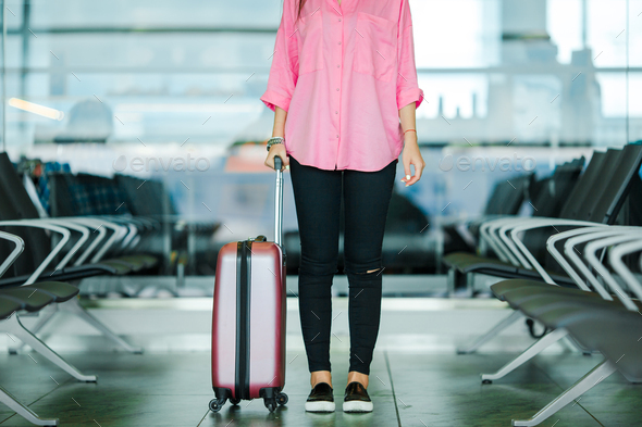 Closeup airplane passenger and pink baggage in an airport lounge waiting for flight aircraft. Young - Stock Photo - Images