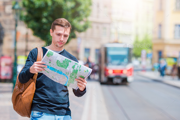 Young man in sunglasses with a city map and backpack in Europe. Caucasian tourist looking at the map - Stock Photo - Images