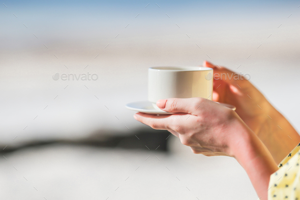 Cup of hot coffee cappuccino in female hands with beautiful view - Stock Photo - Images