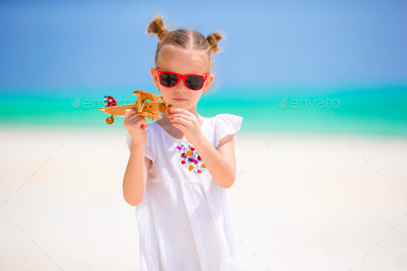 Happy little girl with toy airplane in hands on white sandy beach. Photo travel advertising, flights - Stock Photo - Images