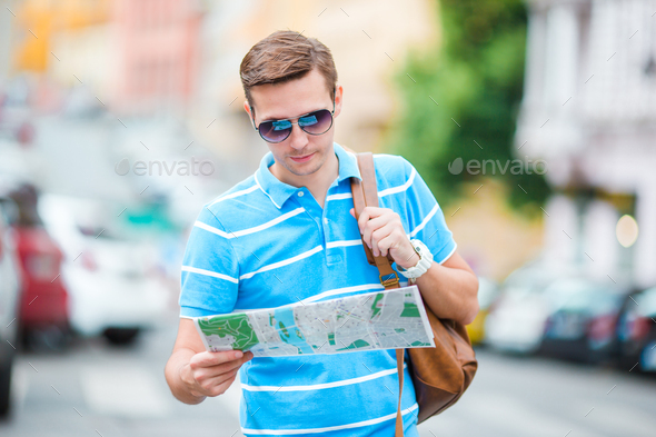 Young caucasian tourist with a city map and backpack in Europe. Happy guy looking at the map of - Stock Photo - Images