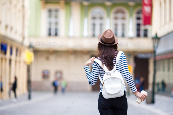 Happy young urban woman drinking coffee in european city. Travel tourist woman with hot drink in - Stock Photo - Images