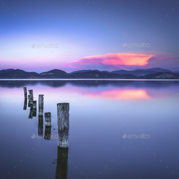Wooden pier or jetty remains on a blue lake sunset. Versilia Tuscany, Italy - Stock Photo - Images