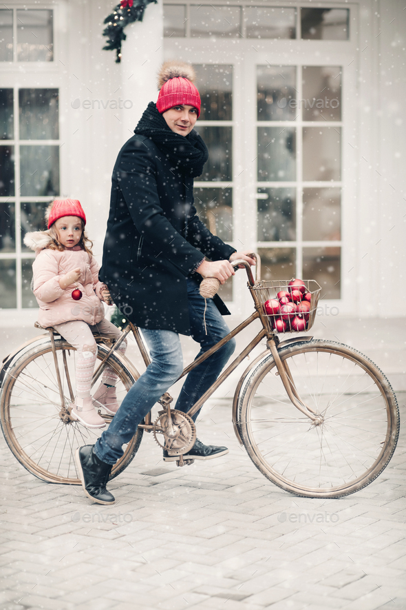 Dad and daughter in red hats riding a bike - Stock Photo - Images